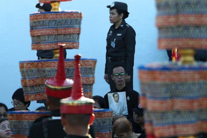 Một người đàn ông cầm di ảnh của cố vương Adulyadej trong buổi tập dượt. Ảnh: REUTERS