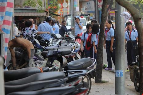 Lực lượng đô thị quận 1 đang lập biên bản cửa hàng đậu xe lấn chiếm vỉa hè làm cho người dân, học sinh tan trường phải đi dưới lòng đường.