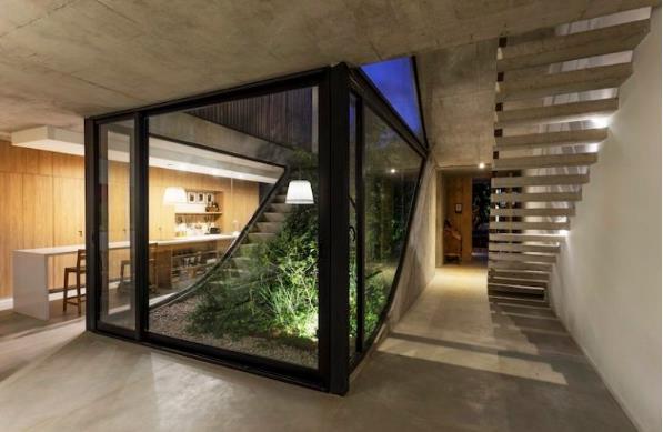 Thiết kế đặc trưng tạo ra sự kết nối liền mạch giữa không gian nội khu và ngoại khu nhà. Khu vườn nhỏ ở tầng 1 có một vài bậc thang dẫn thẳng lên tầng 2.