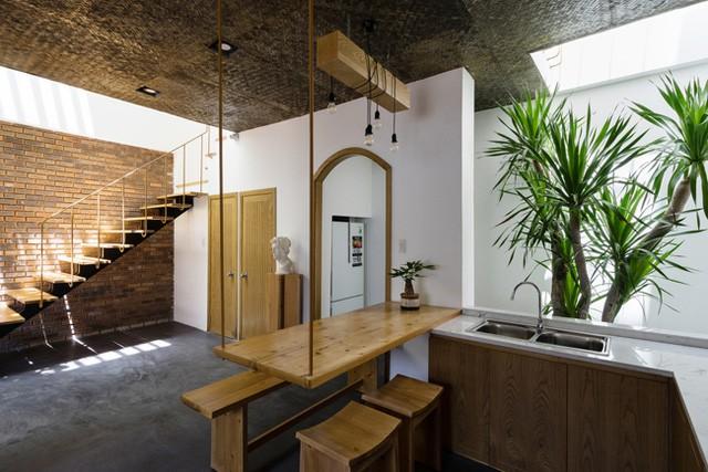 Điểm ấn tượng đặc biệt không thể không nhắc đến trong ngôi nhà này đó là chiếc bàn ăn bằng gỗ 1 đầu được vít chặt vào tường, đầu còn lại được treo lên trần nhà tạo cảm giác khác lạ và đẹp mắt cho không gian.