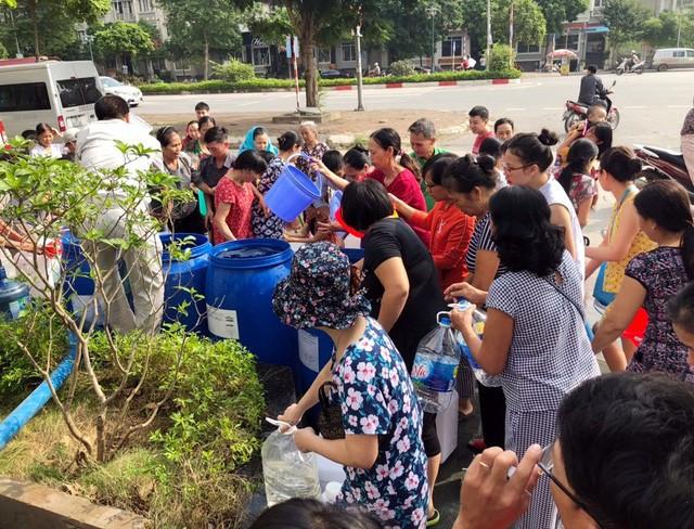 Cư dân mang quần áo giặt giũ, múc nước bể bơi để dùng trong cơn khát ở Hà Nội  - Ảnh 1.