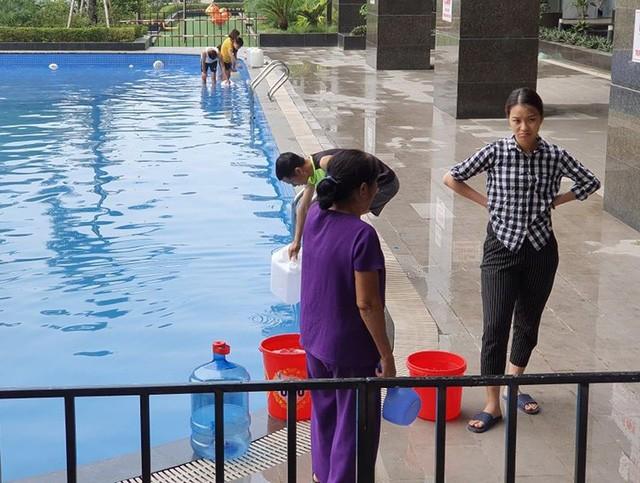 Cư dân mang quần áo giặt giũ, múc nước bể bơi để dùng trong cơn khát ở Hà Nội  - Ảnh 4.