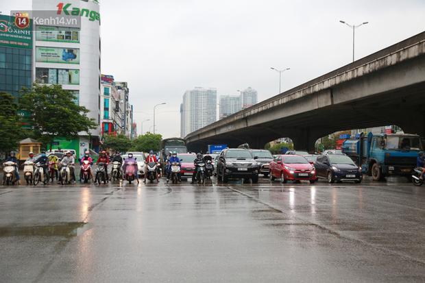 Ảnh: Ngày đầu tiên sau khi nới lỏng cách ly xã hội, đường phố Hà Nội đông đúc kéo dài, người dân chật vật đi làm dưới mưa - Ảnh 1.