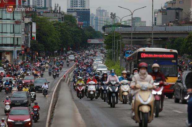 Ảnh: Ngày đầu tiên sau khi nới lỏng cách ly xã hội, đường phố Hà Nội đông đúc kéo dài, người dân chật vật đi làm dưới mưa - Ảnh 11.