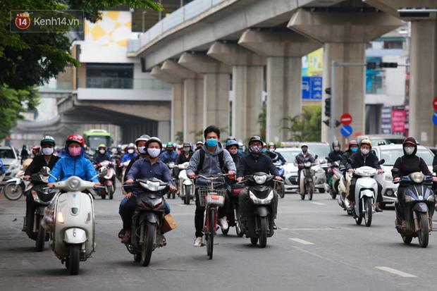 Ảnh: Ngày đầu tiên sau khi nới lỏng cách ly xã hội, đường phố Hà Nội đông đúc kéo dài, người dân chật vật đi làm dưới mưa - Ảnh 10.