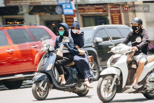 Ảnh: Nhiệt độ ngoài đường tại Hà Nội lên tới 50 độ C, người dân trùm khăn áo kín mít di chuyển trên phố - Ảnh 1.