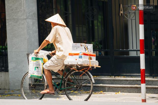 Ảnh: Nhiệt độ ngoài đường tại Hà Nội lên tới 50 độ C, người dân trùm khăn áo kín mít di chuyển trên phố - Ảnh 3.