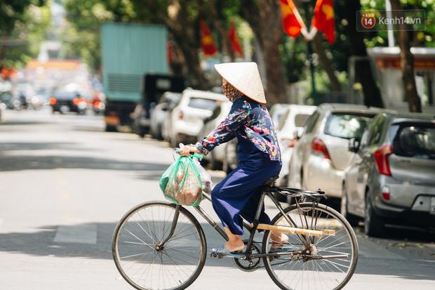 Ảnh: Nhiệt độ ngoài đường tại Hà Nội lên tới 50 độ C, người dân trùm khăn áo kín mít di chuyển trên phố - Ảnh 10.