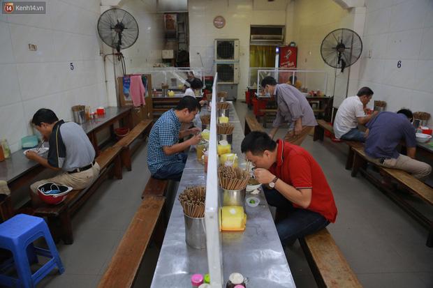 Hà Nội trong ngày đầu tiên giãn cách hàng quán: Bàn được lắp vách ngăn, khách ngồi cách xa nhau hơn 1 mét - Ảnh 16.