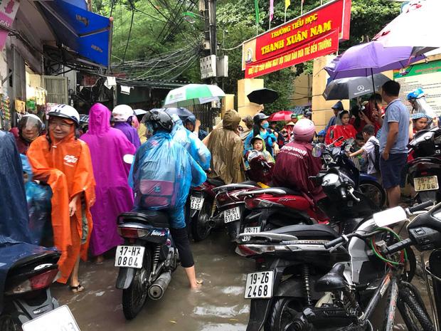 Ảnh: Cơn mưa xối xả đổ xuống Hà Nội giờ tan học khiến nhiều phụ huynh, học sinh mệt nhoài trên đường về nhà - Ảnh 1.