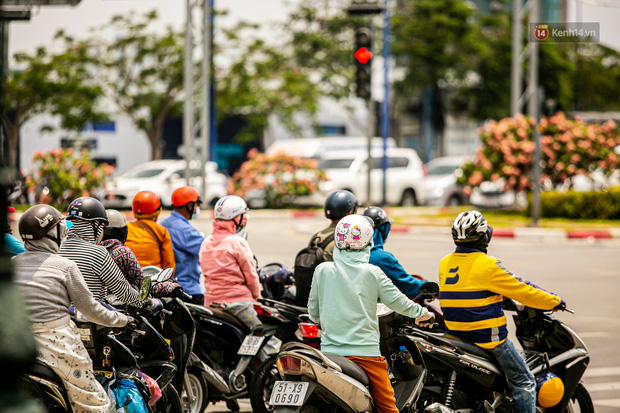 Chùm ảnh: Công nhân vật lộn với cái nóng hầm hập ở Sài Gòn, người đi đường mặc cả áo mưa tránh nắng - Ảnh 1.