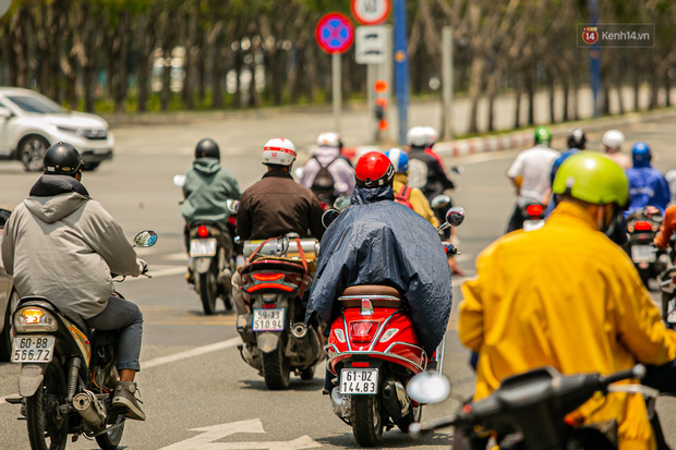 Chùm ảnh: Công nhân vật lộn với cái nóng hầm hập ở Sài Gòn, người đi đường mặc cả áo mưa tránh nắng - Ảnh 11.