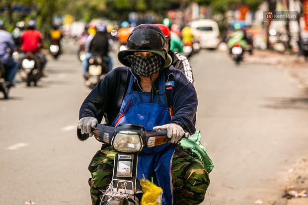 Chùm ảnh: Công nhân vật lộn với cái nóng hầm hập ở Sài Gòn, người đi đường mặc cả áo mưa tránh nắng - Ảnh 13.