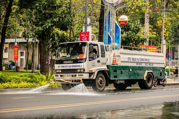 Chùm ảnh: Công nhân vật lộn với cái nóng hầm hập ở Sài Gòn, người đi đường mặc cả áo mưa tránh nắng - Ảnh 3.