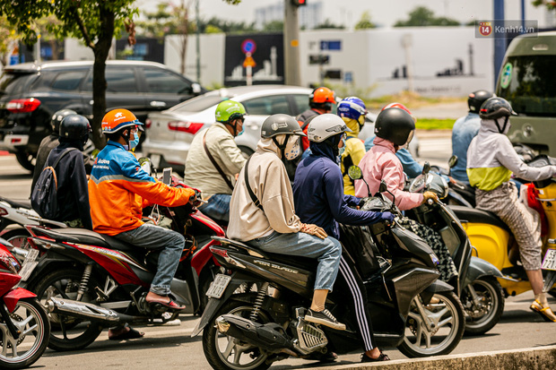 Chùm ảnh: Công nhân vật lộn với cái nóng hầm hập ở Sài Gòn, người đi đường mặc cả áo mưa tránh nắng - Ảnh 10.