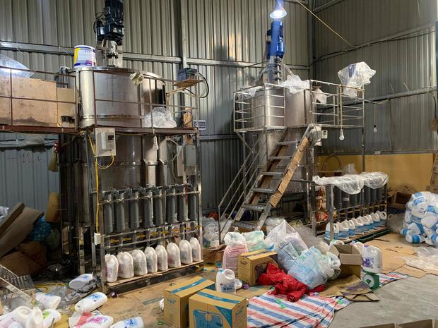Hà Nội: Đột kích xưởng sản xuất quy mô lớn giả nhãn hiệu nước giặt Dnee - Ảnh 6.