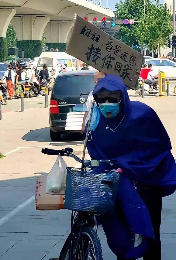Thảm cảnh mưa lũ Trung Quốc: Cụ già mặc áo mưa ngồi cả ngày đợi con gái đã chết đuối ở ga tàu điện, tấm biển bên cạnh đầy xót xa - Ảnh 1.