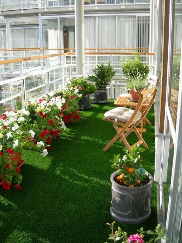 """Để ban công trở nên xanh mát và bắt mắt, ngoài tô điểm bằng cây cảnh bạn có thể phủ một lớp thảm cỏ nhân tạo. Với ý tưởng này ban công nhà bạn sẽ trở thành một """"thiên đường thư giãn"""" ngay trong nhà."""