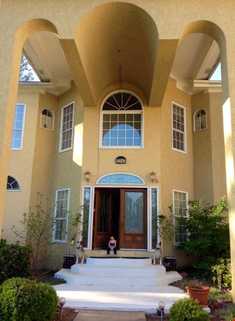 Cửa trước của ngôi nhà với thiết kế kiểu cổ là cửa kính lớn với khung viền gỗ bên ngoài và những thanh sắt hoạ tiết bên trong. Hai bên cửa là hai chú chó bằng sứ đứng canh.