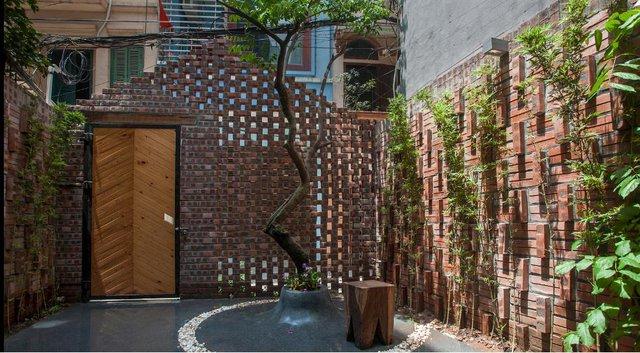 Thật tuyệt vời! Sống giữa nơi đất chật người đông như Hà Nội nhưng chủ nhà có cả một khoảng sân vườn rộng rãi với nhiều cây xanh vô cùng lý tưởng phía trươc nhà. Những lỗ hổng đan xem từ bức tường gạch xây cách điệu vừa giúp thông gió, vừa có khả năng điều hòa không khí trong nhà.