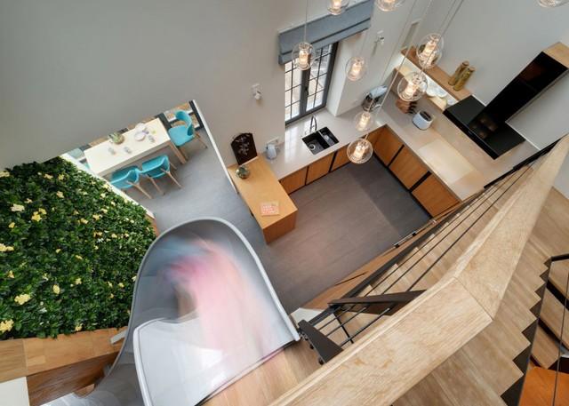 Không gian phòng bếp được thiết kế với nội thất gỗ sáng màu cùng với những chiếc đèn thả trần lạ mắt tạo sự thông thoáng và rộng rãi.