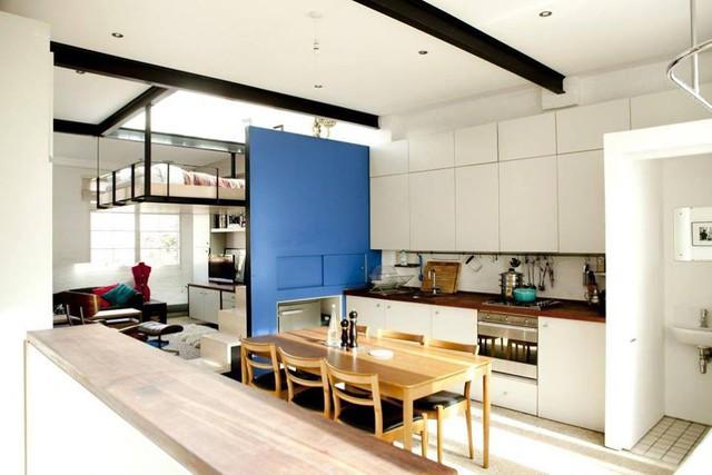Tấm vách ngăn một mặt màu xanh và một mặt màu đen là bức tường duy nhất trong ngôi nhà giúp phân chia không gian giữa khu vực bếp ăn và phòng khách.
