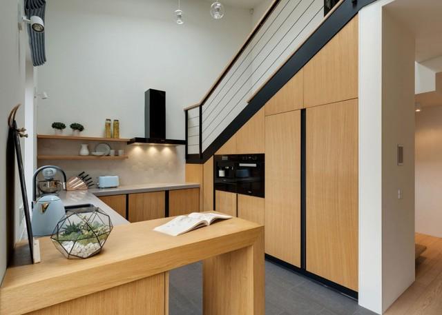 Gầm cầu thang được tận dụng tối đa để làm tủ đựng đồ thêm nơi lưu trữ cho bếp.