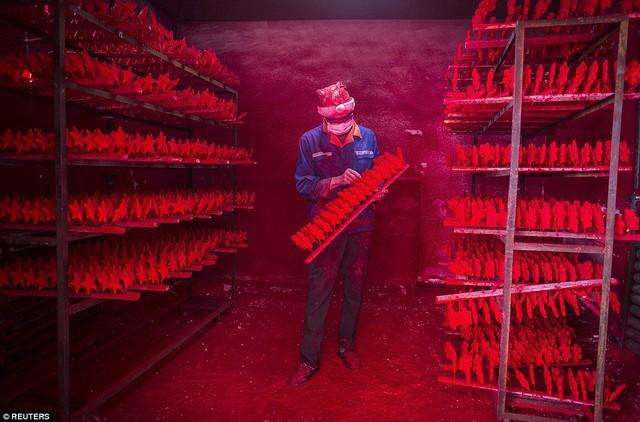 Công nhân làm việc trong một xưởng sơn, nơi tạo ra khoảng 5.000 món đồ trang trí mỗi ngày.