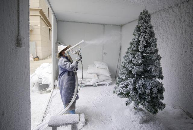 Quá trình phun tuyết giả lên cây thông nhân tạo. Ảnh: Getty