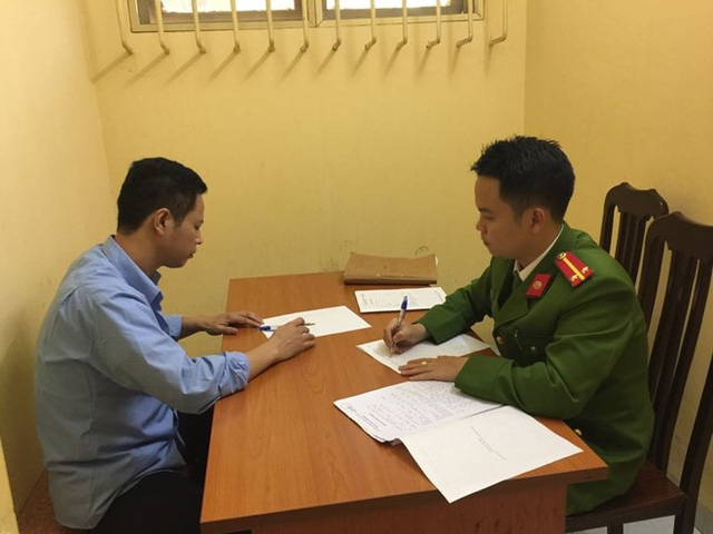 Cán bộ Công an quận Đống Đa lấy lời khai Nguyễn Duy Linh.