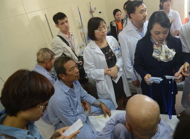 Bộ trưởng Bộ Y tế Nguyễn Thị Kim Tiến (bìa phải) lắng nghe ý kiến bệnh nhân trong chuyến thị sát Bệnh viện