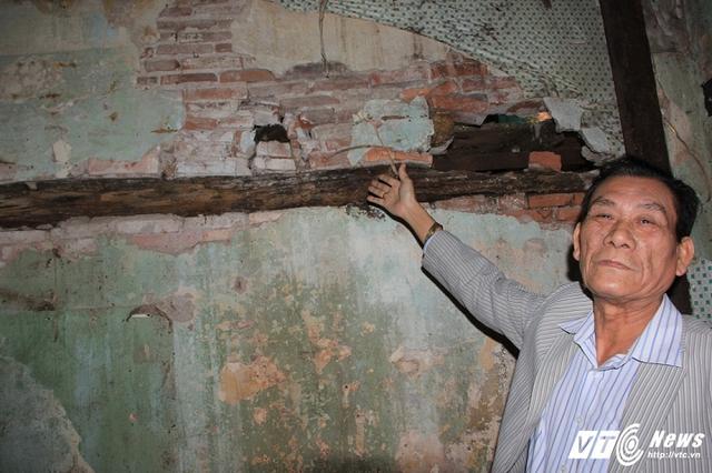 Ông Hải chỉ vào bức tường thủng lỗ chỗ, nứt toác, bong tróc nghiêng sang 1 bên chờ đổ.
