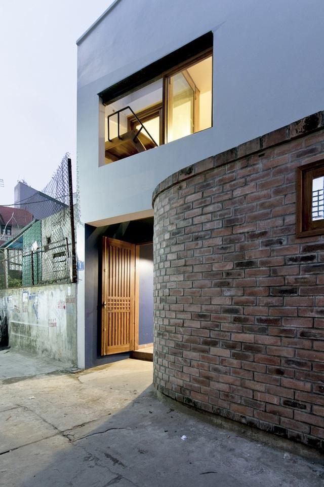 Cửa gỗ được xây lùi vào bên trong, tạo nên khoảng đệm trước khi vào nhà.