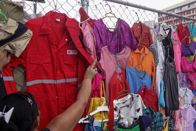 Đồng phục PDVSA được bày bán cùng các loại quần áo khác ở chợ tại thành phố Maracaibo, Venezuela - Ảnh: Reuters