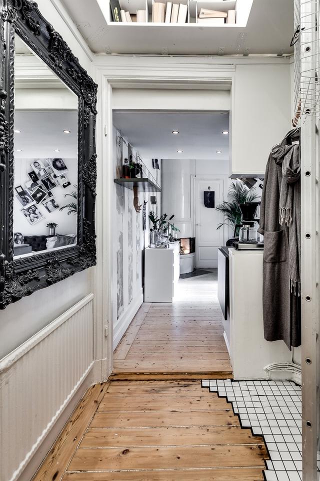 Lối vào nhà còn được treo một tấm gướng lớn giúp nhân đôi không gian nơi góc nhỏ này. Khu vực trống sát trần còn được tận dụng làm giá sách vô cùng tiện nghi.
