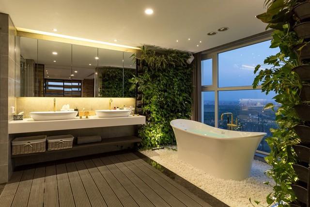 Không gian phòng tắm hiện đại, thoáng sáng và tràn ngập cây xanh. Bồn tắm trắng muốt được rải xung quang lớp sỏi trắng càng khiến không gian nơi đây thêm sang trọng, đẹp mắt.