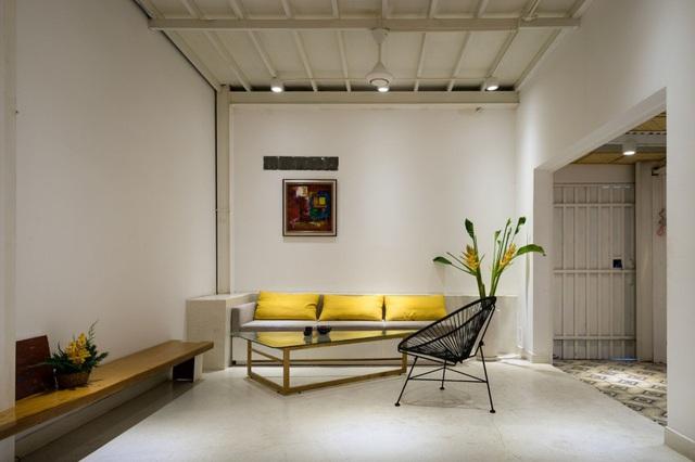 Ngay lối vào là phòng khách được bố trí đơn giản với chiếc bàn trà cách điệu cùng những chiếc gối ôm màu vàng bắt mắt.