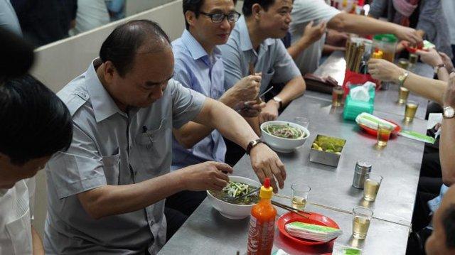 Thủ Tướng Nguyễn Xuân Phúc gọi phở ăn sáng trong lúc kiểm tra an toàn vệ sinh thực phẩm trên đường Nguyễn Hậu, Q.Tân Phú - Ảnh: Thuận Thắng