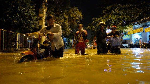 Nhiều người phải dắt bộ qua đoạn đường ngập nặng tại quận 7, TP.HCM - Ảnh: Hữu Thuận