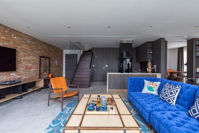 Không gian phòng khách thoáng sáng và tràn ngập ánh sáng tự nhiên nổi bật với ghế sofa xanh giữa nền tường màu tối.