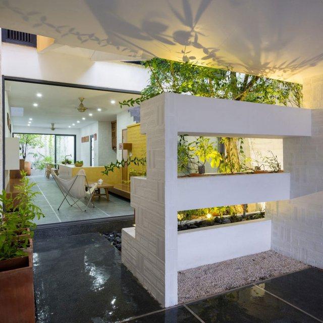 Bên trong là phòng khách, bếp và phòng ăn và sân phơi được ngăn cách với không gian để xe bằng khoảng vườn đệm xinh xắn.