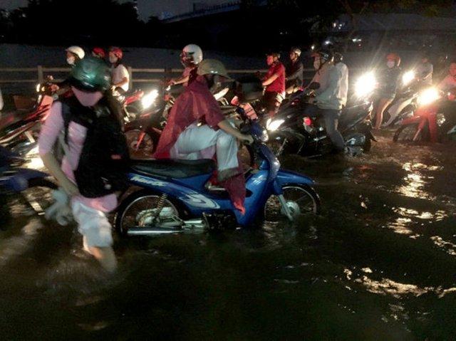 Người đi đường vật vã giữa biển nước ngập tại đường Trần Xuân Soạn - Ảnh: NGỌC KHẢI