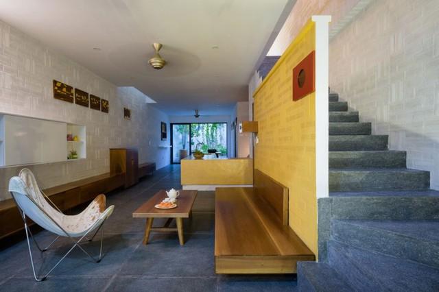 Phòng khách được bài trí với bô bàn ghế gỗ đơn giản cùng bức tường vàng làm sáng bừng cả ngôi nhà.