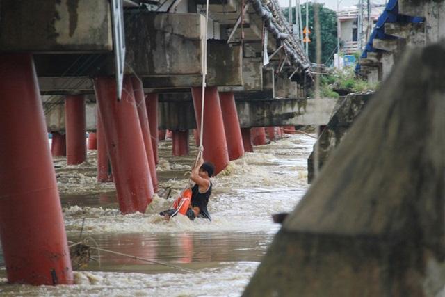 Lực lượng chức năng cứu người bị mắc kẹt giữa nước lũ ở cầu Bóng (TP Nha Trang)
