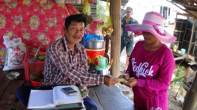 Anh Trung trả tiền cua cho một người Campuchia vừa cân xong- Ảnh:;BỬU ĐẤU
