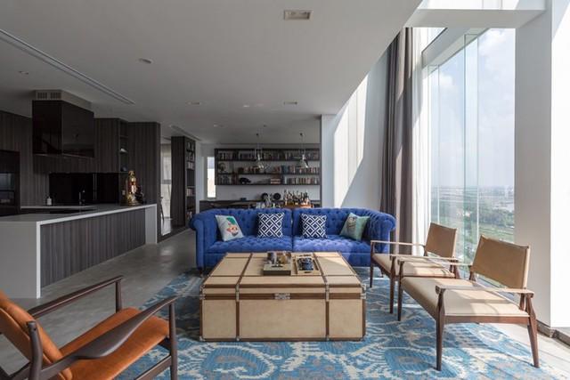 Khu vực bếp ăn được đặt song song với phòng khách được thiết kế theo phong cách tối giản. Toàn bộ hệ thống tủ kệ tại không gian này đều sử dụng tông màu xám-gỗ tạo nên một khối nền tối nổi bật cho phòng khách.