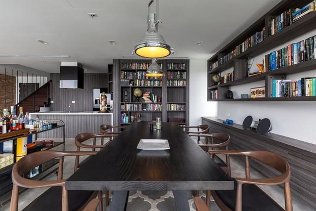 """Bàn ăn lớn với những chiếc ghế cách điệu được đặt ngay sau ghế sofa của phòng khách. Nơi đây vừa có chức năng là bàn ăn nhưng cũng là góc """"thư viện"""" đọc sách lý tưởng cho các thành viên trong gia đình."""