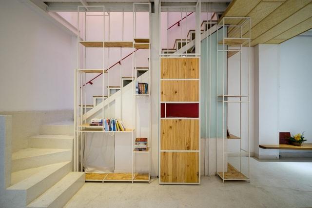 Gầm cầu thang nơi tầng 1 là khu vực vệ sinh được khéo léo ngụy trang bằng những kệ đồ phía ngoài.