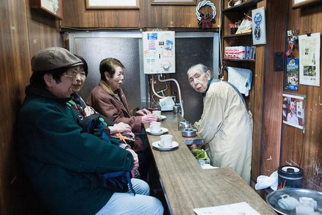 Cụ già làm việc trong cửa hàng nhỏ của mình, phục vụ thực khách những món ăn ngon.