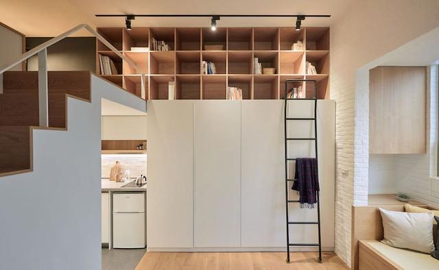Đối diện với nơi làm việc là hệ thống tủ đựng quần áo và giá sách được thiết kế với nhiều ngăn rất tiện lợi. Chiếc thang sắt vừa có chức năng là nơi vắt đồ dùng cá nhân vừa giúp chủ nhà dàng lấy sách trên giá khi cần.